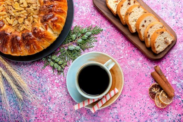 Bovenaanzicht heerlijke rozijnencake met kopje koffie op lichtroze oppervlak bak taart suiker zoet koekje koekjeskleur