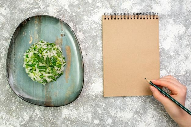 Bovenaanzicht heerlijke salade bestaat uit greens en kool binnen plaat