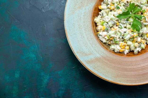 Bovenaanzicht heerlijke salade binnen ronde plaat op het donkerblauwe bureau.