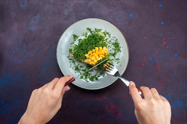 Bovenaanzicht heerlijke salade met mayyonaise likdoorns greens en kip in plaat op donker bureau.