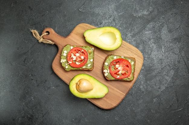 Bovenaanzicht heerlijke sandwiches met avocado en rode tomaten op grijze achtergrond snack maaltijd hamburger sandwich brood