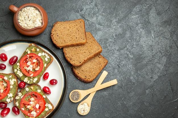 Bovenaanzicht heerlijke sandwiches met avocado pasta en tomaten in plaat op de grijze achtergrond broodje hamburger sandwich snack brood