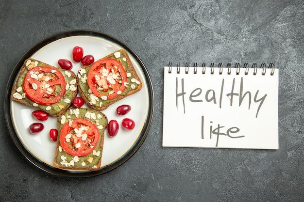 Bovenaanzicht heerlijke sandwiches met gesneden tomaten en gezond leven schrijven op grijs oppervlak snack broodje hamburger sandwich brood