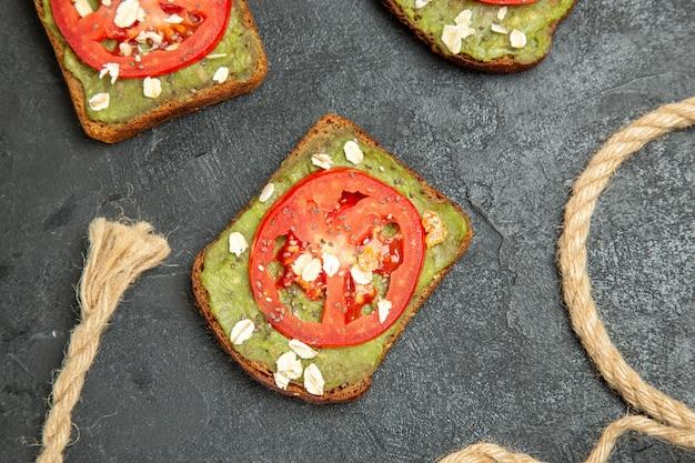 Bovenaanzicht heerlijke sandwiches met wassabi en rode tomaten op grijs oppervlak maaltijd hamburger sandwich snackbroodje