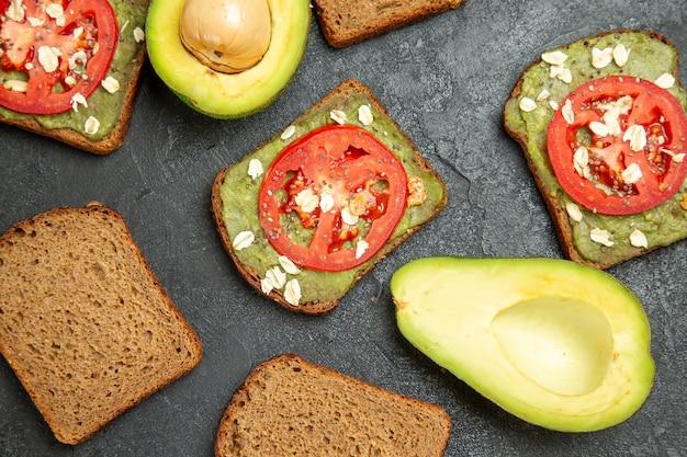 Bovenaanzicht heerlijke sandwiches met wassabi en rode tomaten op grijs oppervlak snack maaltijd hamburger sandwich brood