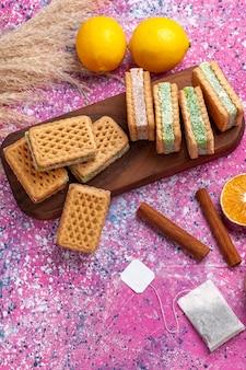 Bovenaanzicht heerlijke sandwichkoekjes met citroen en kaneel op het roze bureau.