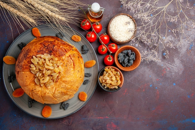 Bovenaanzicht heerlijke shakh plov gekookte rijstmaaltijd met rozijnen en tomaten op donkere achtergrond maaltijd deeg rijst diner