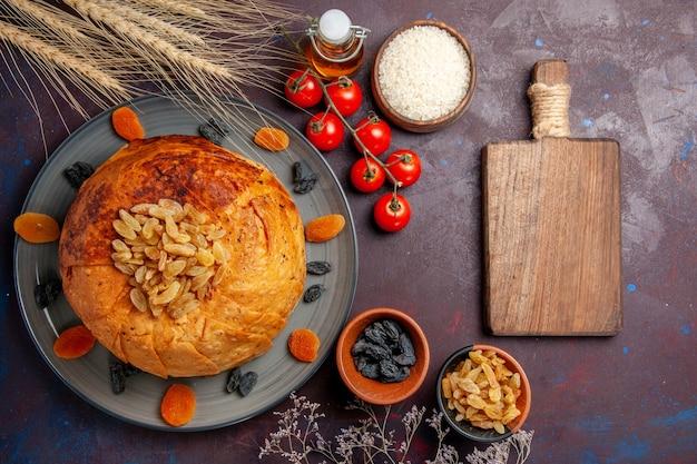 Bovenaanzicht heerlijke shakh plov gekookte rijstmaaltijd met rozijnen en tomaten op het donkere achtergrondmaaltijddeeg koken rijstdiner