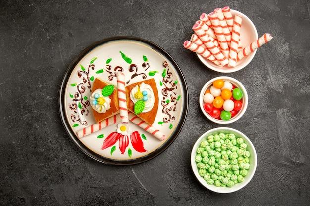 Bovenaanzicht heerlijke slagroomtaart binnen ontworpen bord met snoepjes op de donkere achtergrondcake, zoete koekjesroomtaart