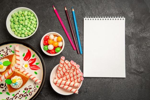 Bovenaanzicht heerlijke slagroomtaart in ontworpen bord met snoepjes op donkere achtergrond, zoete koekjesroomsuikertaarttaart