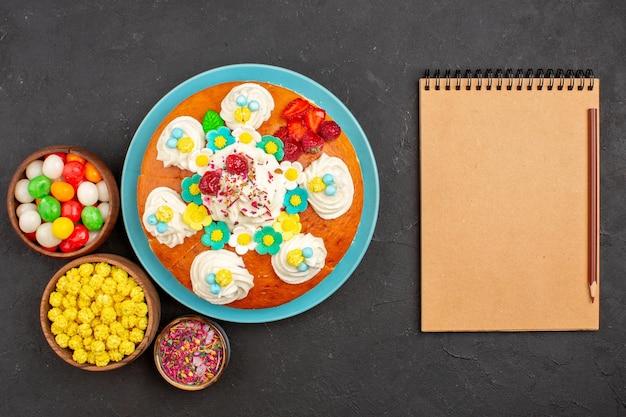 Bovenaanzicht heerlijke slagroomtaart met fruit en snoep op de donkere achtergrond taartkoekje, zoete theekoekjestaart