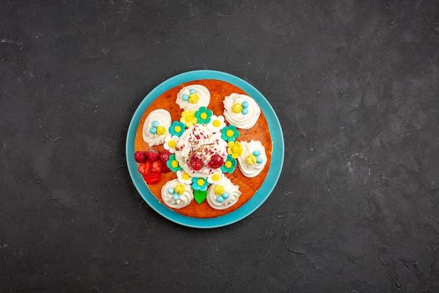 Bovenaanzicht heerlijke slagroomtaart met fruit op een donkere achtergrond, zoete koekjestaart, koekjescake-thee
