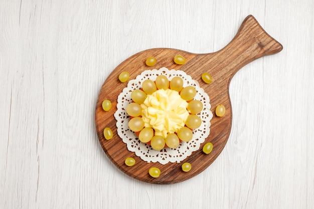 Bovenaanzicht heerlijke slagroomtaart met groene druiven op wit bureau fruit dessert cake biscuit taart