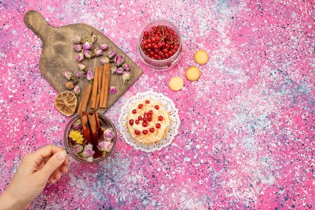 Bovenaanzicht heerlijke slagroomtaart met verse rode veenbessen samen met kaneel en thee op het paarse bureau