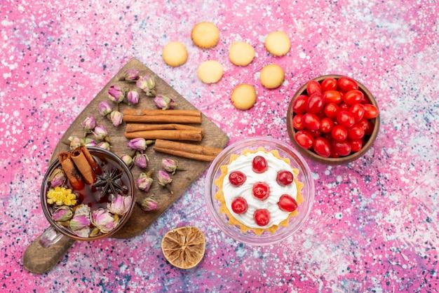 Bovenaanzicht heerlijke slagroomtaart met verse rode veenbessen samen met kaneelkoekjes en thee op het paarse suikergoed