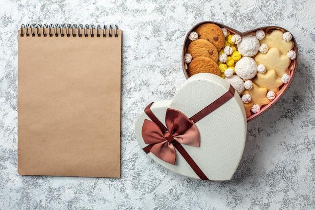 Bovenaanzicht heerlijke snoepjes, koekjes, koekjes en snoepjes in een hartvormige doos op een witte oppervlakte, suikertaart, zoet lekker