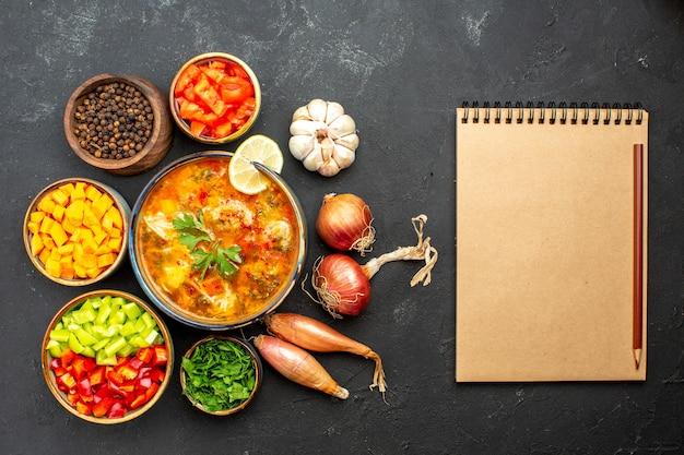 Bovenaanzicht heerlijke soep met greens en groenten op grijze vloer soep maaltijd vlees soep saus diner