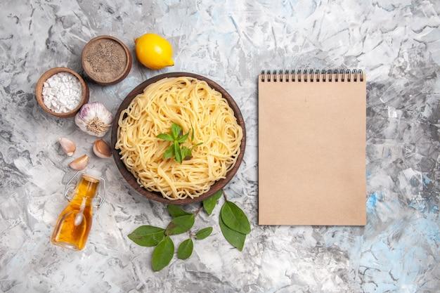 Bovenaanzicht heerlijke spaghetti binnen plaat op witte tafel maaltijdschotel pasta