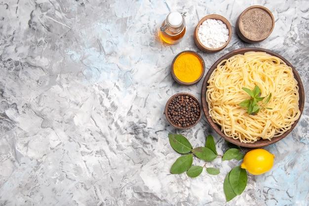 Bovenaanzicht heerlijke spaghetti met smaakmakers op een witte vloer maaltijd deeg schotel pasta