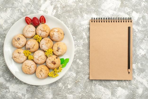 Bovenaanzicht heerlijke suikerkoekjes binnen plaat op de witte cake van de het koekthee van het achtergrondsuikerkoekje