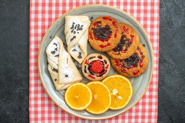 Bovenaanzicht heerlijke suikerkoekjes met gebak en sinaasappel op donkere oppervlakte cake suikerkoekje zoete koekjes thee