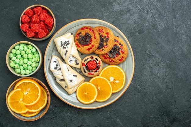Bovenaanzicht heerlijke suikerkoekjes met gebak en stukjes sinaasappel op donkere oppervlakte suikerkoekje zoete cake koekjes thee