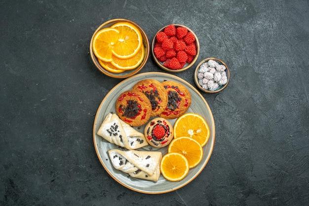 Bovenaanzicht heerlijke suikerkoekjes met gebak en stukjes sinaasappel op donkere oppervlakte suikerkoekje, zoete cakekoekjesthee