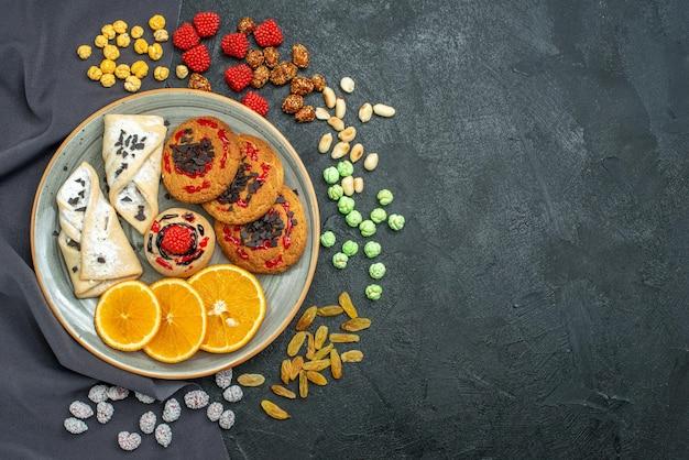 Bovenaanzicht heerlijke suikerkoekjes met gebak en stukjes sinaasappel op donkere oppervlakte suikerkoekje, zoete koekjestheecake
