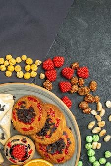 Bovenaanzicht heerlijke suikerkoekjes met gebak en stukjes sinaasappel op donkere vloer suikerkoekje zoete koekjes cake thee