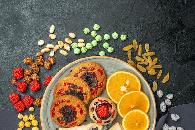 Bovenaanzicht heerlijke suikerkoekjes met gebak en stukjes sinaasappel op het donkere oppervlak suikerkoekje zoete koekjes cake thee