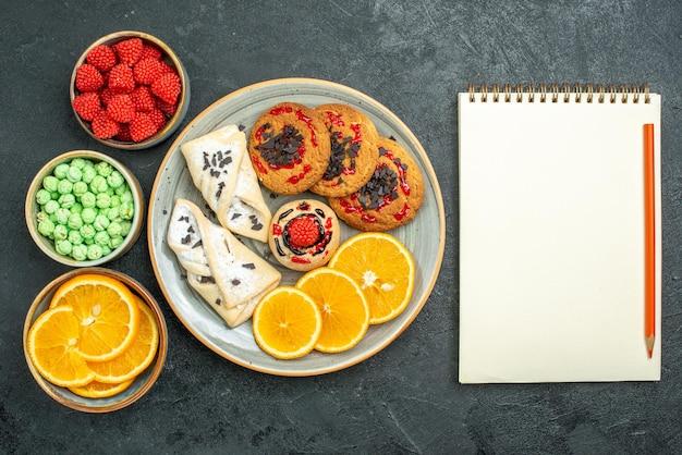 Bovenaanzicht heerlijke suikerkoekjes met gebak notitieblok en stukjes sinaasappel op donkere oppervlakte suikerkoekje zoete cake koekjesthee