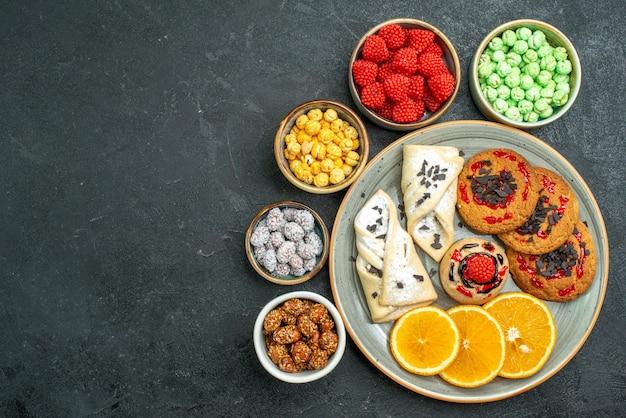Bovenaanzicht heerlijke suikerkoekjes met gebak, snoepjes en sinaasappelschijfjes op donkere oppervlakte suikerkoekje, zoete cakekoekjesthee