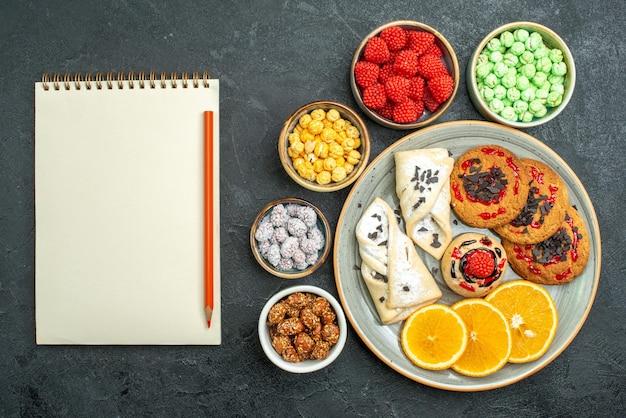 Bovenaanzicht heerlijke suikerkoekjes met gebak, snoepjes en stukjes sinaasappel op een donkere oppervlakte, suikerkoekje, zoete koekjestheecake
