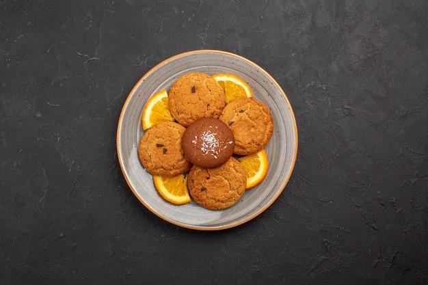 Bovenaanzicht heerlijke suikerkoekjes met gesneden sinaasappels in een bord op een donkere achtergrond, suikerfruitkoekje, zoet koekje