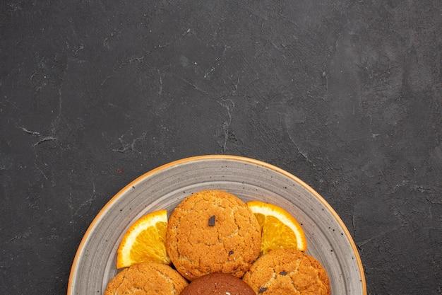 Bovenaanzicht heerlijke suikerkoekjes met gesneden sinaasappels in plaat op donkere achtergrond suikerkoekje zoet koekjesfruit