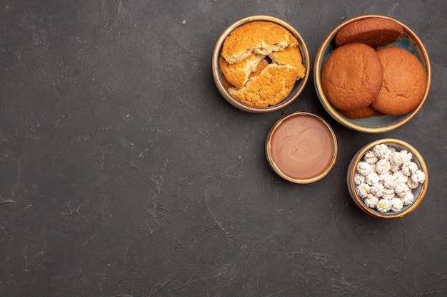 Bovenaanzicht heerlijke suikerkoekjes met snoepjes op donkere achtergrond biscuit suikerkoekje zoet
