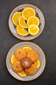 Bovenaanzicht heerlijke suikerkoekjes met vers gesneden sinaasappels op donkere bureausuikerkoekjes zoet koekjesfruit