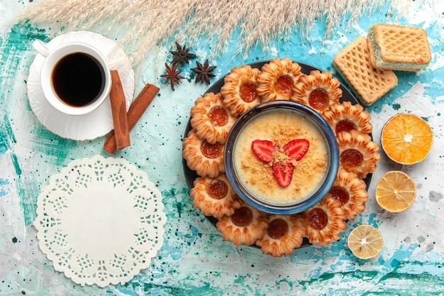 Bovenaanzicht heerlijke suikerkoekjes met wafels, kopje koffie en aardbeiendessert op blauwe vloer, koekjeskoekje, zoete cake, dessertkleur