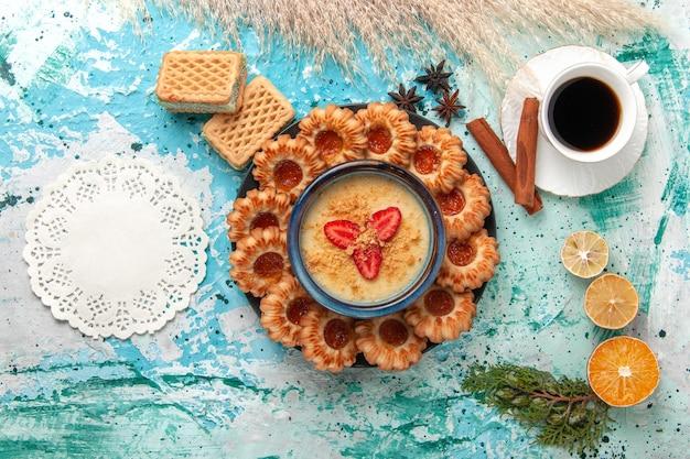 Bovenaanzicht heerlijke suikerkoekjes met wafels, kopje koffie en aardbeiendessert op het blauwe bureau