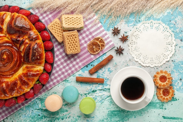Bovenaanzicht heerlijke taart met aardbeien en wafels op lichtblauw oppervlak