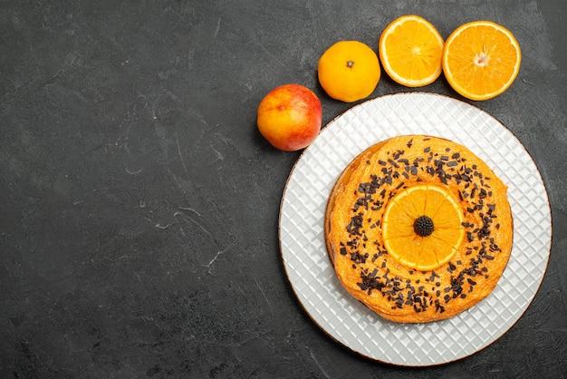 Bovenaanzicht heerlijke taart met chocoladeschilfers en stukjes sinaasappel op donkere oppervlakte fruit dessert taart cake biscuit thee