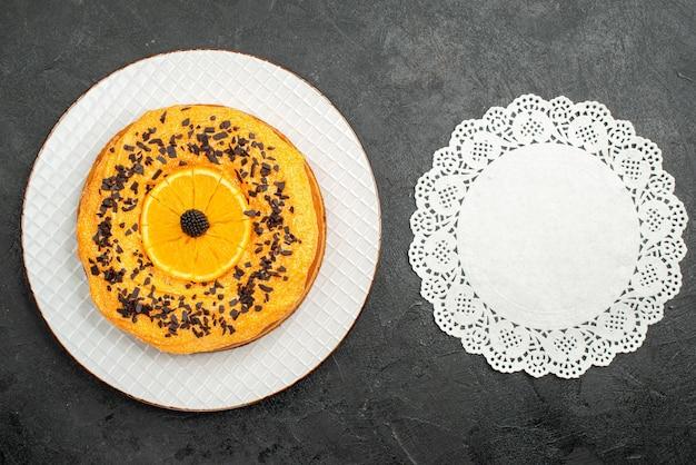 Bovenaanzicht heerlijke taart met chocoladeschilfers en stukjes sinaasappel op donkere oppervlakte fruit dessert thee taart cake biscuit