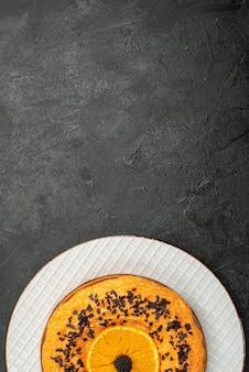 Bovenaanzicht heerlijke taart met chocoladeschilfers en stukjes sinaasappel op donkere vloer taart dessert cake thee fruit biscuit