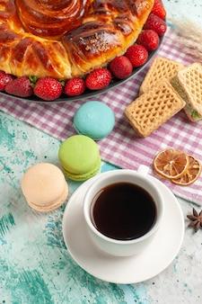 Bovenaanzicht heerlijke taart met kopje thee en verse rode aardbeien op blauwe ondergrond