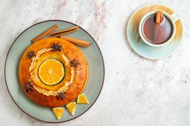 Bovenaanzicht heerlijke taart met kopje thee op witte achtergrond fruit zoete noot cake taart biscuit
