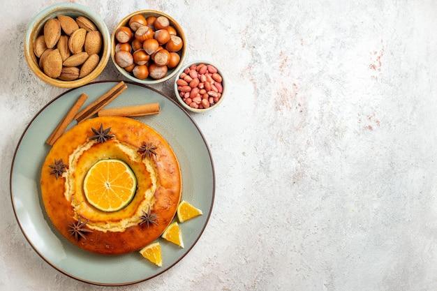 Bovenaanzicht heerlijke taart met noten en verse citrusvruchten op witte achtergrond fruit zoete noot cake taart biscuit