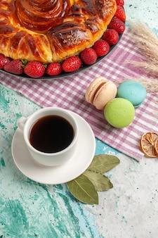 Bovenaanzicht heerlijke taart met rode aardbeien en kopje thee op blauwe ondergrond