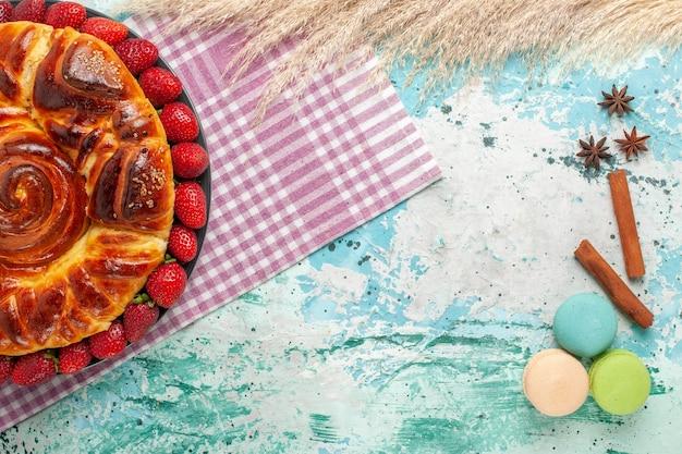 Bovenaanzicht heerlijke taart met rode aardbeien en macarons op blauwe ondergrond