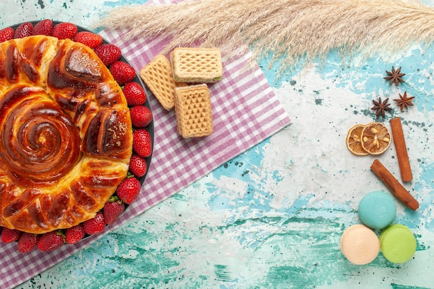 Bovenaanzicht heerlijke taart met rode aardbeien en wafels op het blauwe oppervlak