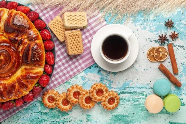 Bovenaanzicht heerlijke taart met rode aardbeien koekjes en wafels op blauwe ondergrond